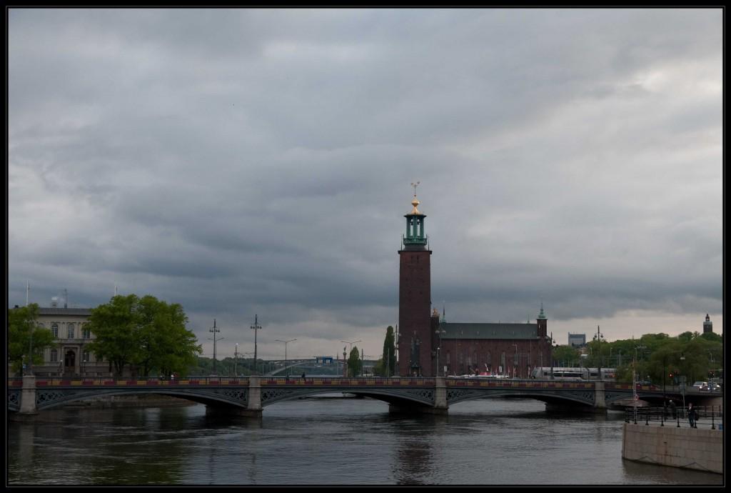 Das Rathaus Stockholms bei bedrohlichem, von dunklen Wolken verhangenen Himmel von einer Brücke fotografiert. Das Rathaus besitzt einen sehr hohen Turm mit einer goldenen Verzierung auf dem Dach.