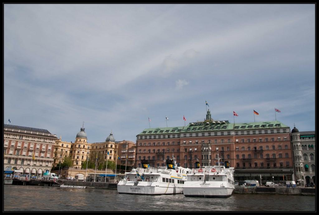 Das Grand Hotel Stockholm ein fünfstöckiges rotes Backsteingebäude mit Kupferdach, auf dem eine Fahnen und der Schriftzug Grand Hotel Stockholm thronen. Links neben dem Grand Hotel ein gelbliches Gebäude mit Türmchen und Türmen, die den Zwiebeltürmen etwas ähnlich sehen.
