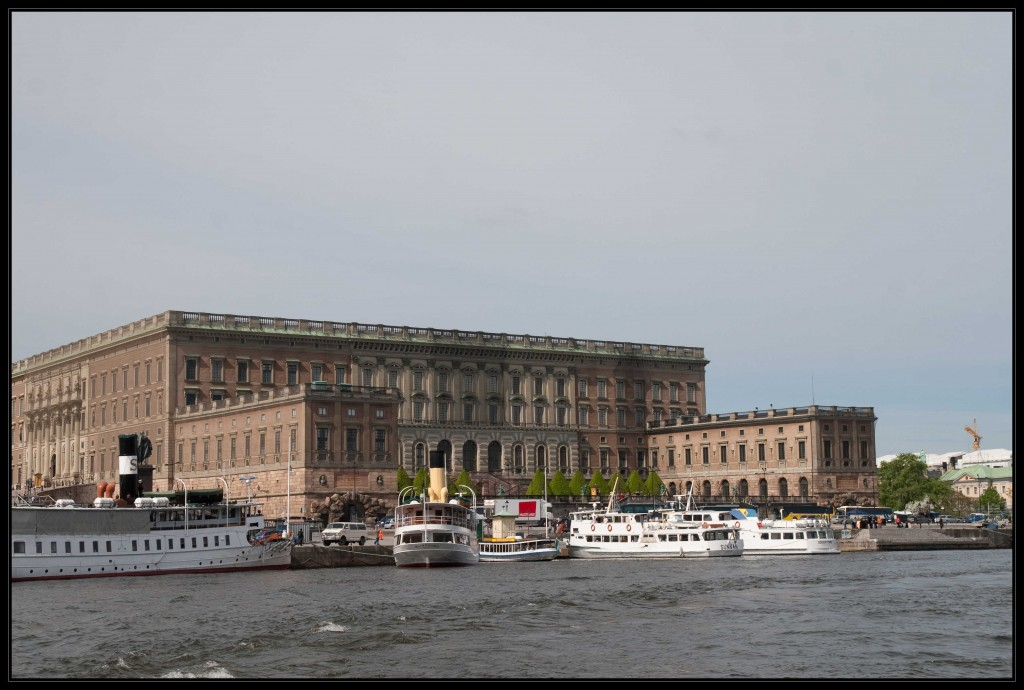 Eine Seite des königlichen Palasts, mit Wasserfällen die aus zwei Giebeln rauschen. Vor dem braunen Gebäude in Gamla Stan ist ein Fahrgastschiff zu sehen.