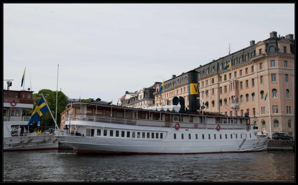 Ein nostalgisches Ausflugsschiff im Stockholmer Stadthafen mit einem riesigen schwarzen Schornstein, den in der Mitte ein dickes gelbes Farbband ziert. Am Heck des Schiffes weht eine schwedische Fahne im Wind.