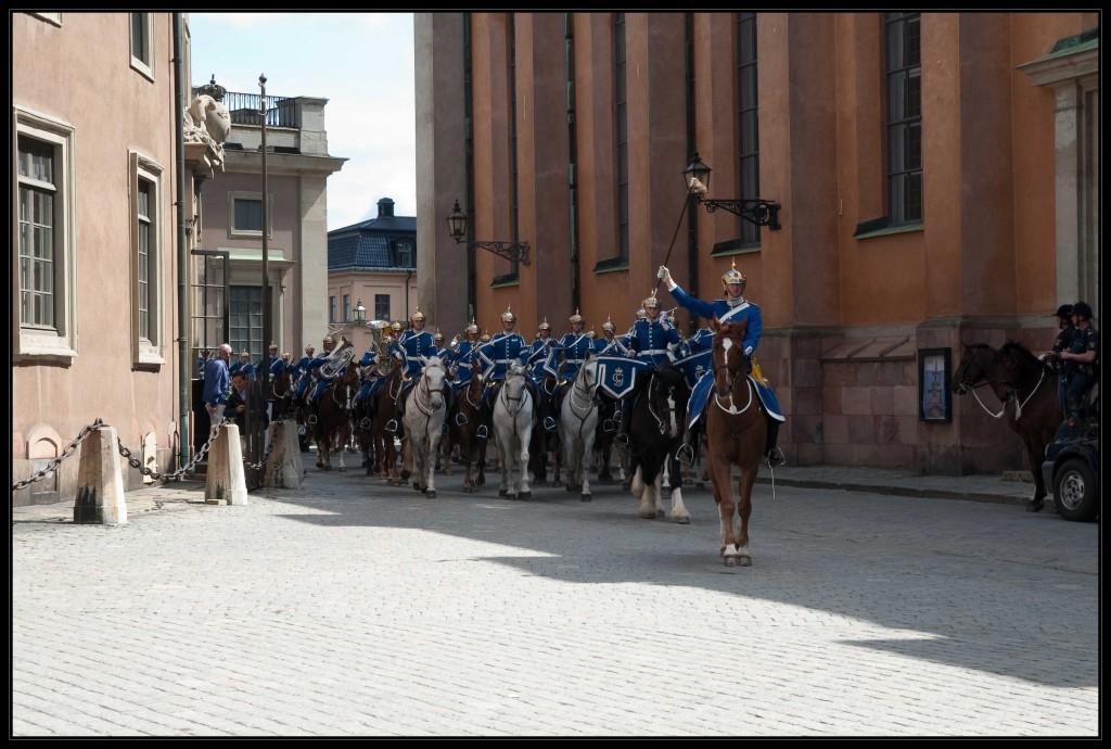 Blau gekleidete Reiter mit silbernen Helmen, die zur Wachablösung in den Hof des königlichen Schlosses reiten. Angeführt von einem einzelnen braunen und einem schwarzen Pferd folgen 4 Schimmel und anschließend viele weitere sehr ansehnliche braune Pferde in einer Viererformation