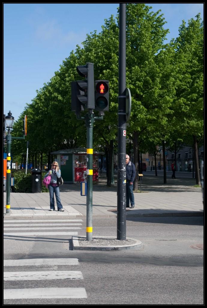 Typische Blindenampel in Stockholm, mit einem dunkelgrünen Mast, der gelbe Markierungen enthält. Außerdem der blaue Anforderungskasten, der nach innen zeigend angebracht ist. Die Fahrbahn, bzw. der Übergang ist mit einem Zebrastreifen markiert.