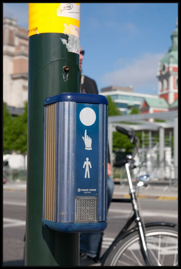 Der Anforderungskasten einer Blindenampel in Stockholm. Blau mit einem weißen Männchen, einer weißen Hand sowie einem weißem Punkt an der Seite. Unterhalb dieser Symbole ein Reflektor.