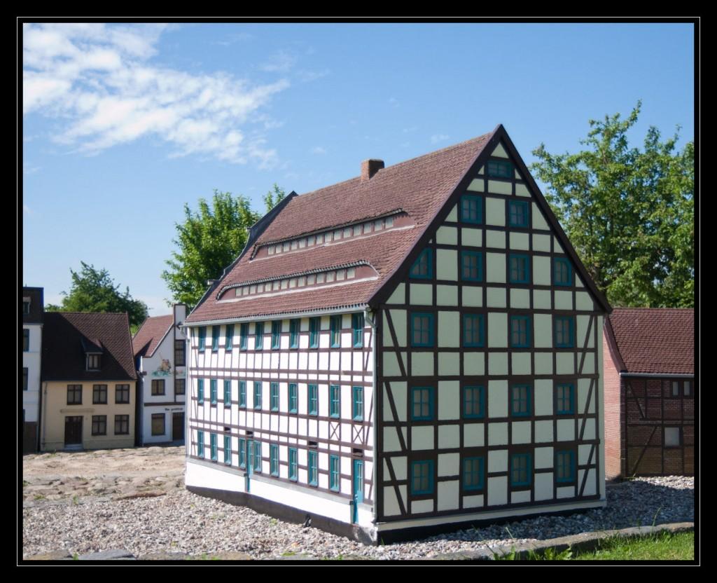 Foto: Ein dreistöckiges Fachwerkhaus mit einem Spitzdach. Das Haus wurde schräg von der Seite fotografiert. Das Dach zeigt 2 übereinander liegende lange schmale Gauben, die sich fast über die gesamte Breite des Hauses erstrecken. Die Fensterrahmen des Hauses sind blau.