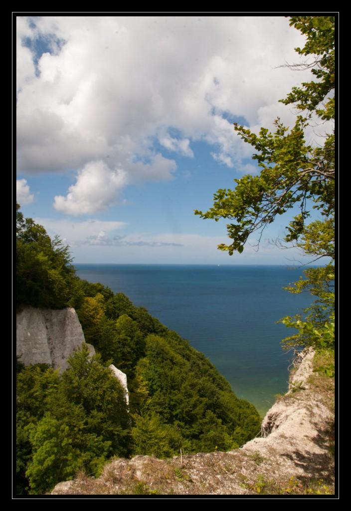 Foto: Ein Blick vom Königsstuhl, links im Bild ein Teil des Kreidefelsens mit viel Grün. In der Ferne leuchtet die blaue Ostsee.