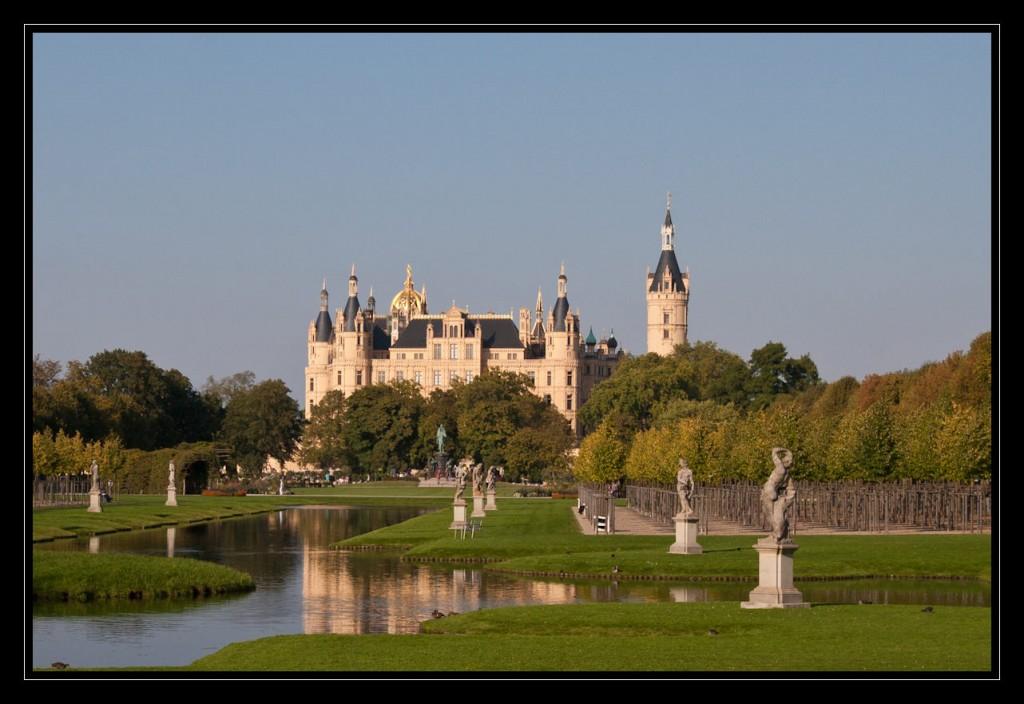 Foto: Das Schweriner Schloss bei strahlend blauem Himmel im warmen Sonnenlicht. Die gelbe Farbe des Schlosses und, die goldenen Verzierungen und Türme wirken märchenhaft. Das Schloss steht hinter dem Schlossgarten, welcher am rechten Bildrand von Bäumen gesäumt ist. Links davon einige Skulpturen und künstlich angelegte Wasserläufe in denen sich das Schloss spiegelt. Rings herum eine grüne Wiese.