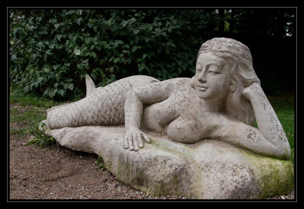 Foto: Im Garten der Villa Seebach liegt eine steinerne Seenixe, die mit ihrer linken Hand ihren Kopf mit dem langen Haar stützt. Ihren rechten Arm hat sie unterhalb ihres Busens um ihren Bauch geschlungen.