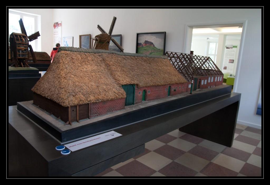 Modell eines Geesthardenhauses, das im linken Teil das Bildes ein mit Reet gedecktes Dach, das rote Mauerwerk sowie grüne Türen zeigt. Rechts ist der Dachstuhl offen und lässt einen Blick in das Innere des Hauses zu. Links vor dem Modell befinden sich die Tags.