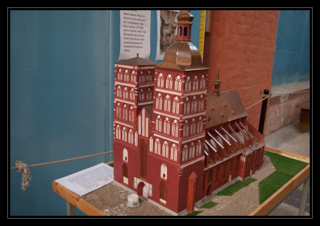 Foto: Tastmodell St. Nikolai. Es zeigt die zwei imposanten Türme, die das mittlere Kirchenschiff einfassen. Der rechte Turm besitzt eine Turmspitze, die den Wetterhahn trägt. Der linke Turm hingegen ist abgeflacht. Das Modell zeigt das Backsteinmauerwerk und das kupferfarbene Dach.