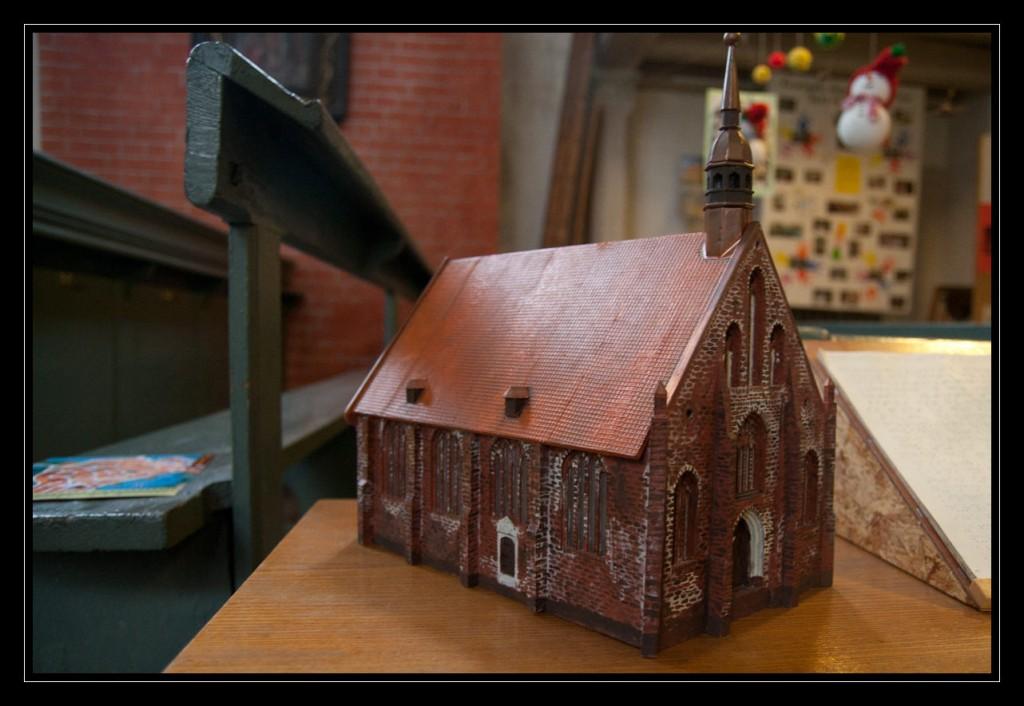 Foto: Tastmodell der Heilgeistkirche. Das Foto zeigt die Heilgeistkirche von schräg von vorn, so dass die linke Seite der Kirche ebenfalls vollständig zu sehen ist. Das detaillierte Modell zeigt die Mauersteine sowie die Dachziegel dieser eher kleinen Kirche sehr deutlich.