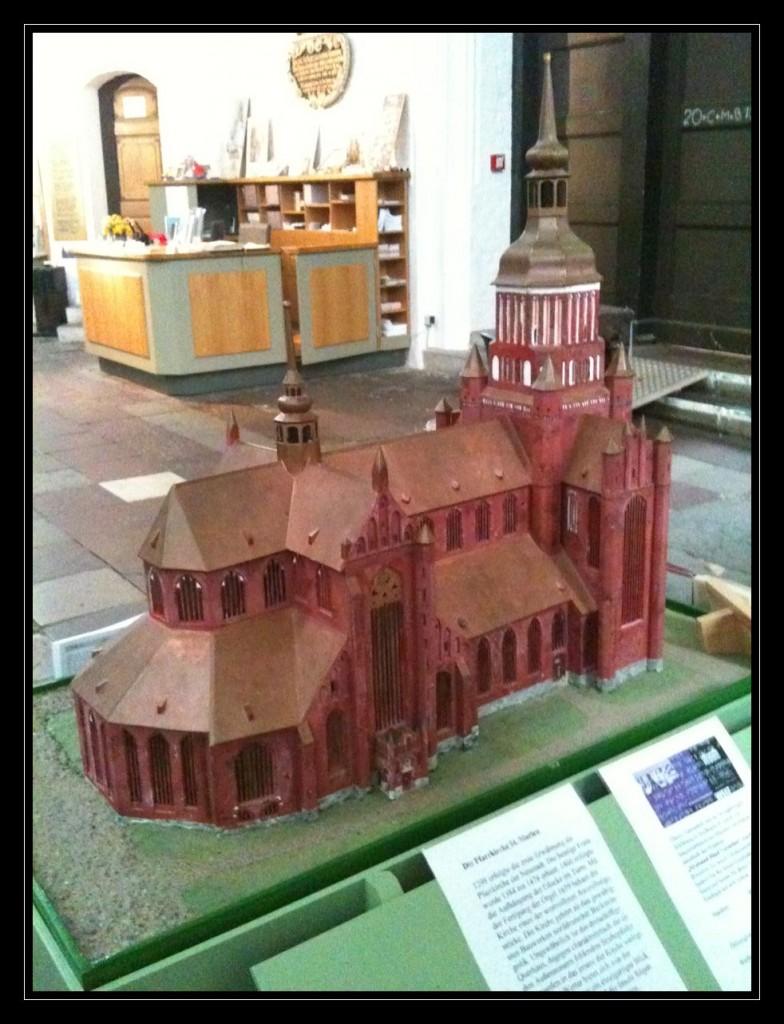 Foto: Tastmodell der St. Marienkirche von schräg hinten aufgenommen, so dass eine komplette Seite der Kirche mit dem aufwendigen Dach zu sehen ist. Die Mauern der Kirche sind rot und das Dach nebst der Turmspitzen bronze.