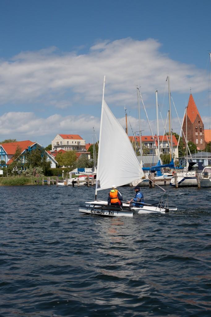 Der Combi-Tri fährt in den Hafen von Rerik. Jana hat dabei die Ruderpinne fest in der Hand. Im Hintergrund sieht man die Silhouette Reriks.