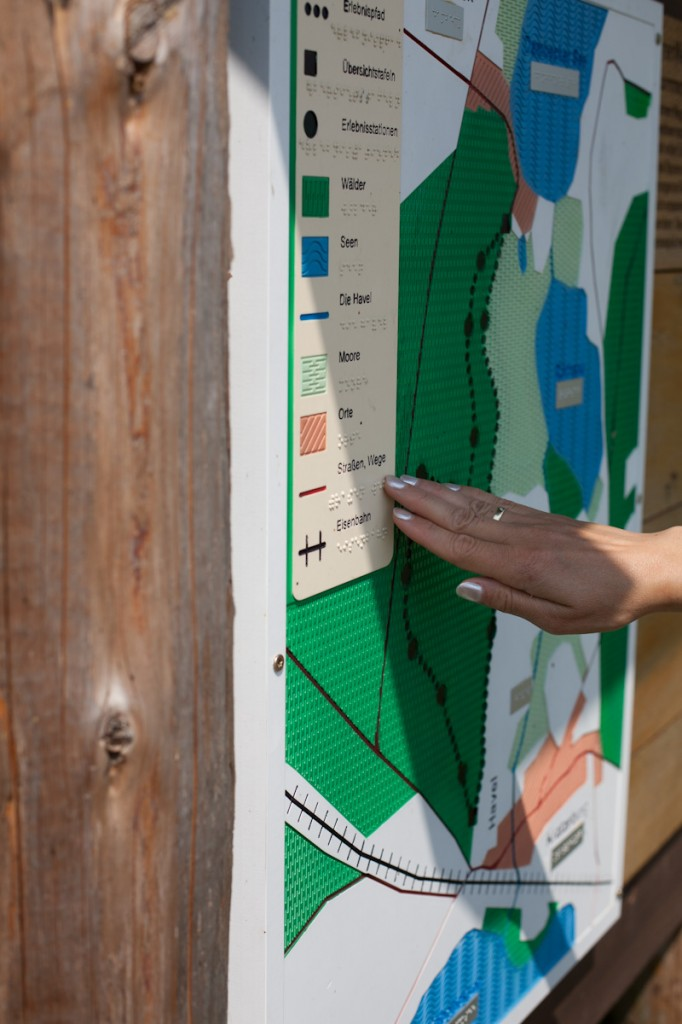 Bild: Der Tastplan zu Beginn des Spurenwegs. Schön ausgearbeitet reliefartige Strukturen für Moore, Wald und Wasser werden von Janas Finger erspürt.