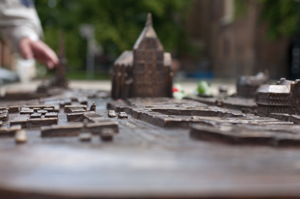 Bild: In der Mitte des Bildes fahren zwei Autos auf einer Strasse. Diese sind sehr schön ausgearbeitet. Im Hintergrund, etwas unscharf, ein weiteres historisches Bauwerk.