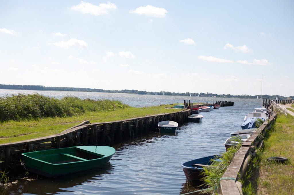 Bild: Ein Kanal, gesäumt von bunten Motor- und Ruderbooten bildet den Ludwigsburger Hafen. Links vom Kanal erstreckt sich eine satt grüne Wiese, an die ein Schilfgürtel angrenzt. In weiter Ferner erkennt man die Silouette Greifswalds.