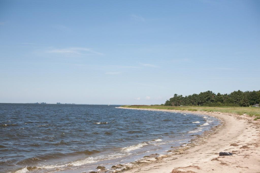 Bild: Das Wasser schneidet sich sichelförmig von links in den schmalen Naturstrand. In weiter Ferner einige Bäume und strahlend blauer Himmel.