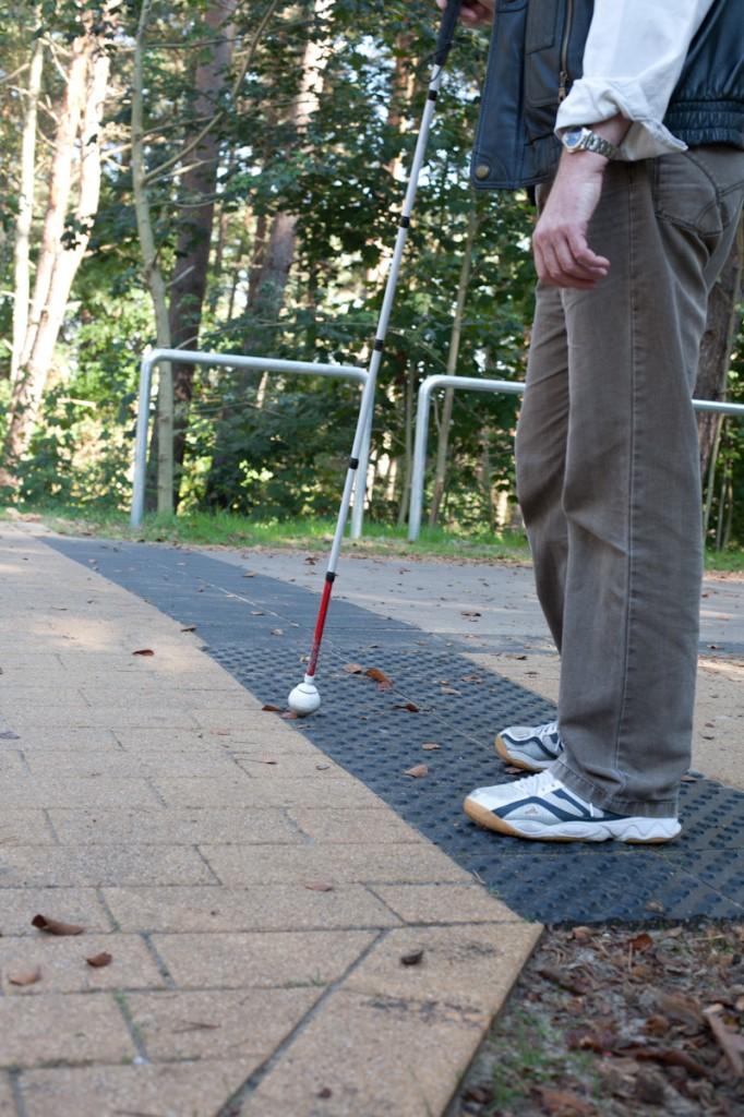 Bild: Eine Person steht mit ihrem Langstock auf der Noppenplatte. Im Hintergrund endet der quer über den Radweg verlaufende Markierungsstreifen an einem silberfarbenen Gitter, das eine Abgrenzung des Strandzugangs bildet. Dieser befindet sich jedoch links vom Gitter.