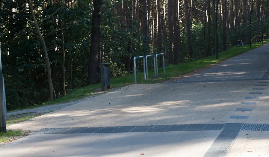 Bild: Zwei Markierungsstreifen führen quer über Fuß- und Radweg. Sie bilden den Beginn und das ende eines Strandaufgangs. Rad- und Fußweg sind ebenfalls durch einen Markierungsstreifen getrennt. Auf dem ockerfarbenen Fußweg befindet sich jeweils Noppenplatten.