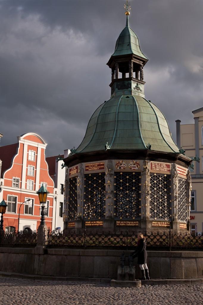 Foto: Jana erfühlt Nix und Nixe an der Wismarer Wasserkunst. Während graue Wolken am Himmel aufziehen tauchen die Strahlen der tiefstehenden Sonne das Gold der Wasserkunst und Janas Haare in ein warmes, goldenes Licht. Im Hintergrund sind auch noch einige Giebel von historischen Stadthäusern zu sehen, deren Farben leuchten.