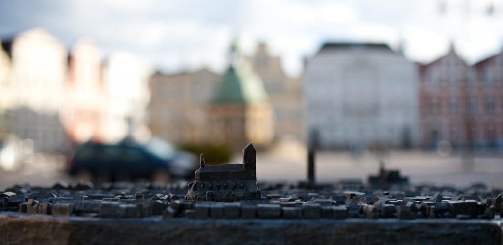 Foto: Scharf im Vordergrund das Tastmodell mit der sich deutlich erhebenden St. Nicolaikirche und dem Marienkirchturm. In Unschärfe verschwimmt in weiter Ferne die Wasserkunst auf dem Wismarer Marktplatz.