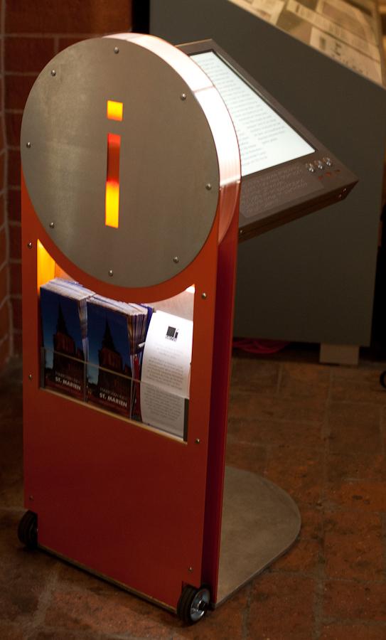 Foto: Sacris spricht für sich selbst - des Informationssystem ist in der seitlichen Ansicht wie ein i gestaltet. Der untere Teil des i's ist orange während der i-Punkt aus Aluminium gefertigt ist. Er enthält wiederum ein orange leuchtendes i. Die obere Rundung des i's leuchtet in einem hellen weiß.