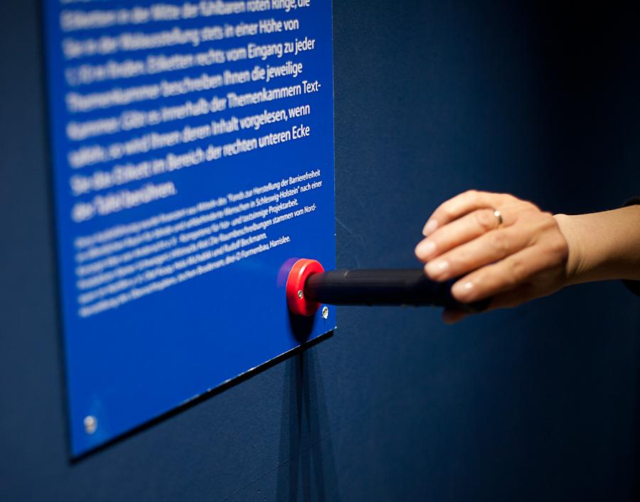 Foto: Der Hörstift wird in einen roten, trichterförmigen erhabenen Kreis eingeführt. Im Hintergrund erkennt man eine Informationstafel, welche weiße Schrift auf blauem Grund enthält.