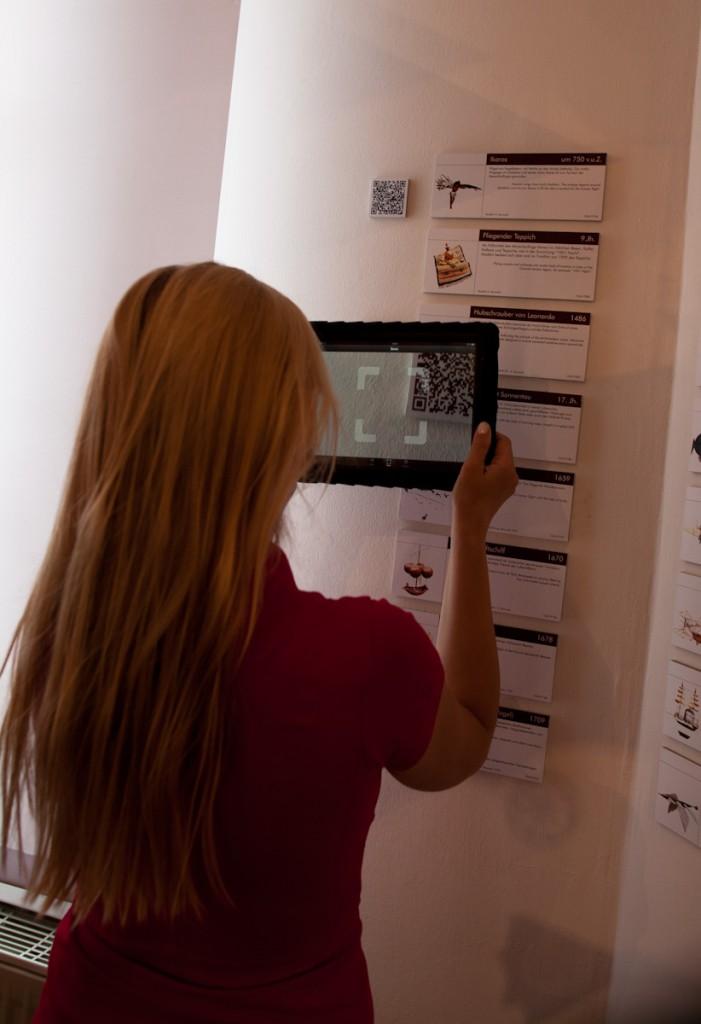 Jana beim Scannen eines QR-Codes. Im Display des iPads erscheint im rechten oberen Teil ein QR Code.