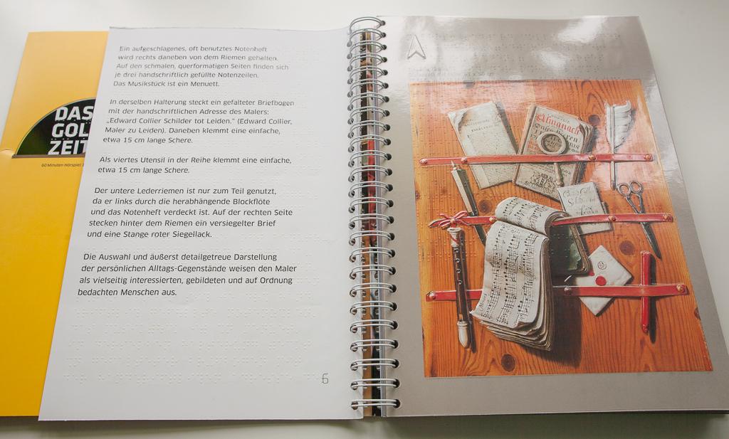 """Foto: Aufgeschlagenes Buch - links Bildbeschreibungen in Braille- und Schwarzschrift, rechts das Bild """"Steckbrett mit Flöte"""""""