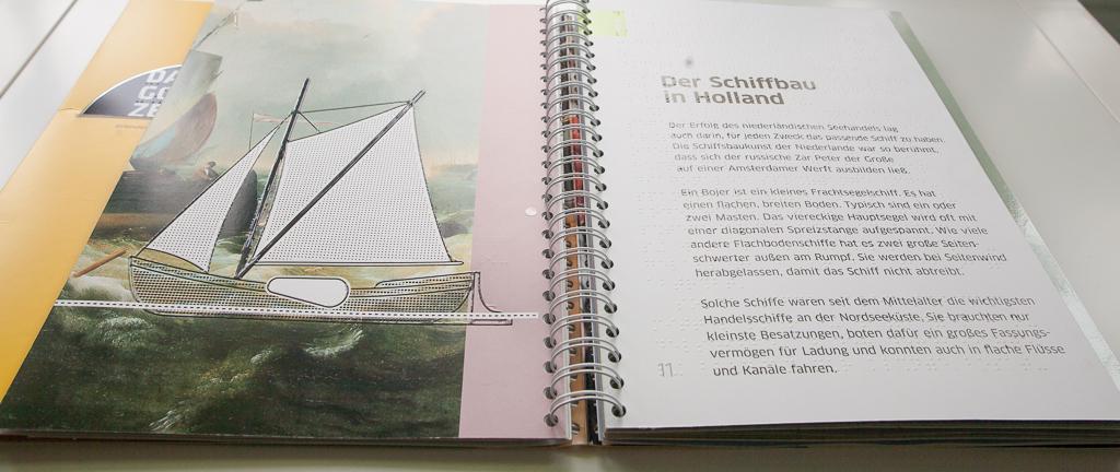 Foto: Aufgeschlagenes Buch - links eine Detaildarstellung eines Segelboots in Siebdruck, rechts Braille- und Schwarzschrift