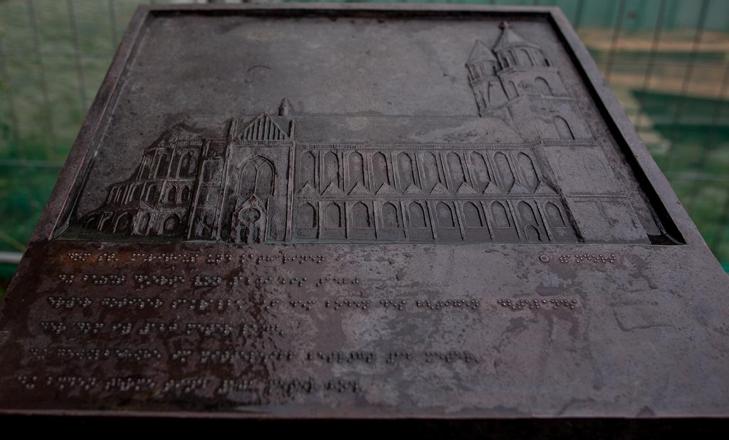 Foto: Bronzerelief des Magdeburger Doms auf einem Steinsockel. Das Relief zeigt den Dom in einer seitlichen Ansicht, darunter Brailleschrift.