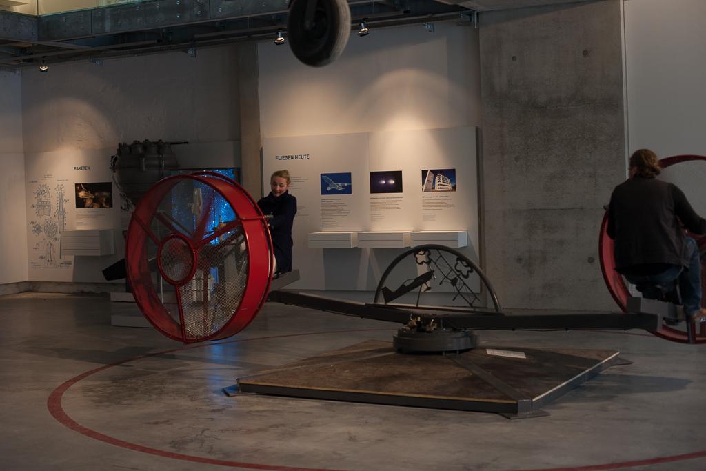 Foto: Jana und Herr Quade in Aktion. Per Muskelkraft werden die riesigen in rote Käfige gesperrten Propeller in Bewegung gesetzt, welche wiederum die beiden auf einer Kreisbahn in Bewegung setzen.