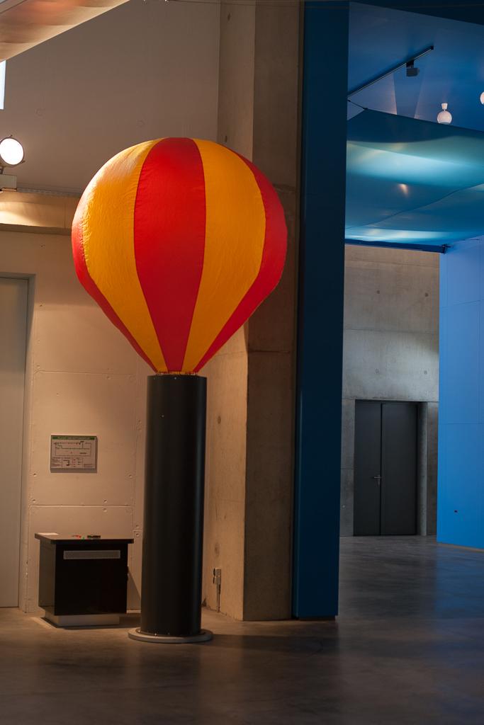 Foto: Der ca. 2m große rotorange gestreifte Heißluftballon ruht auf einem ca. 2,50m hohen grauen Rohr, aus dem heiße Luft in den Ballon einströmt. Neben dem Rohr befindet sich ein Pult, dass die Bedienung der Experimentieranlage mittels 2 Knöpfen ermöglicht.