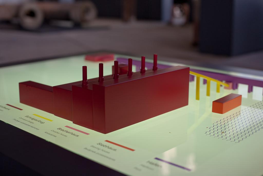 Foto: Modell des Kraftwerksgeländes Im Vordergrund befindet sich das in Rot modellierte Kraftwerk, aus dem 6 Schornsteine empor ragen. Der in Unschärfe getauchte Hintergrund zeigt in Gelb den Schrägaufzug sowie in lila die Kranbrücke, welche zum Brecherhaus führt.