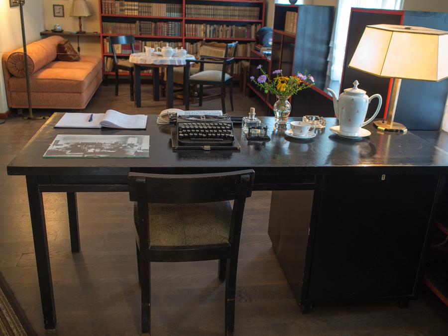Foto: Der schwarze Schreibtisch mit einer alten Schreibmaschine, rechts davon ein Tintenfass, eine Vase mit bunten Blümchen, eine Kaffeekanne sowie eine Schreibtischlampe. Im Hintergrund ist eine Sitzgruppe und eine Bücherwand zu sehen.