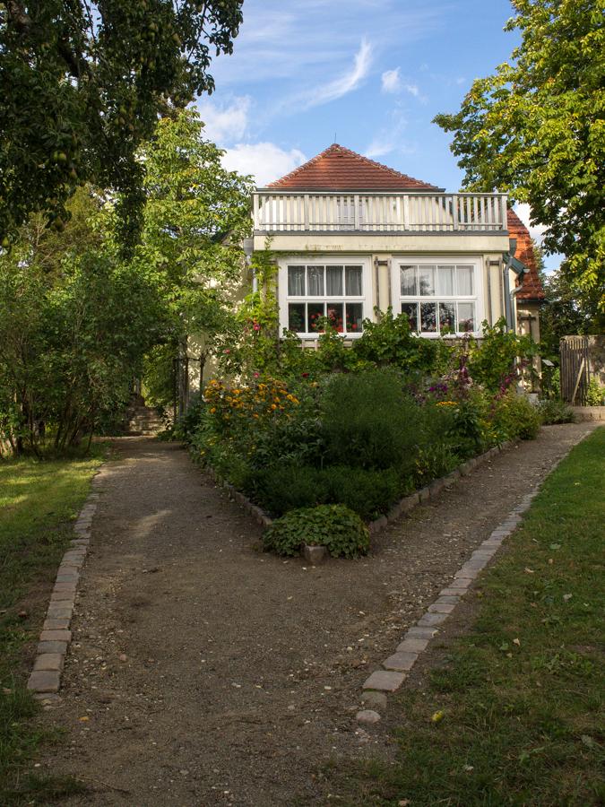 Foto: Das Dreiecksbeet auf dem Fallada Anwesen mit Blick auf den Giebel des Hauses.
