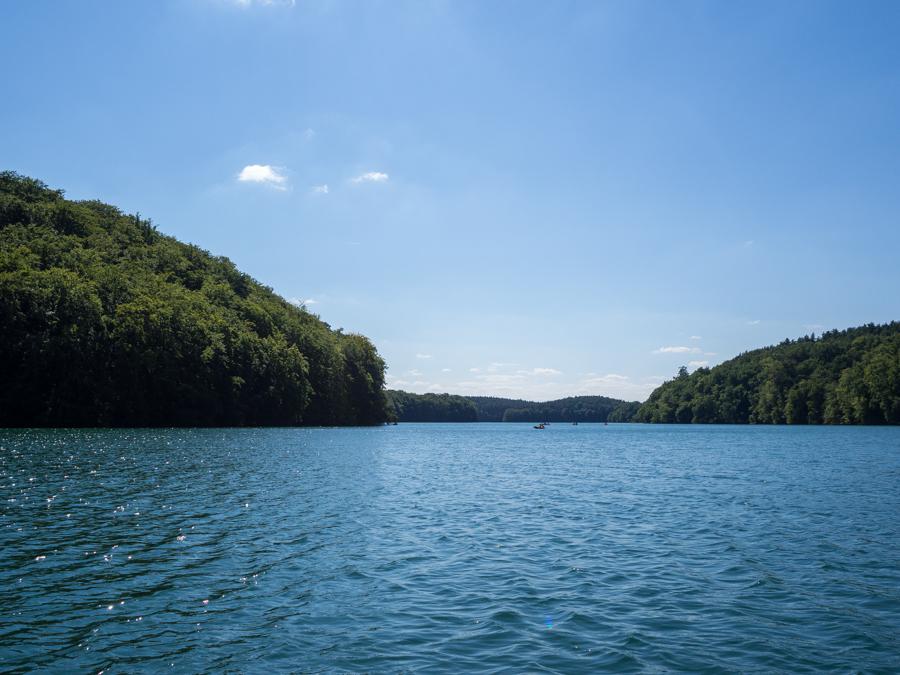 Foto: Blick auf den Schmalen Luzin, links und rechts von ihm erheben sich majestätisch Wälder auf Hügeln. Auf dem türkisfarbenen Wasser tummeln sich in weiter Ferner einige Kajaks.