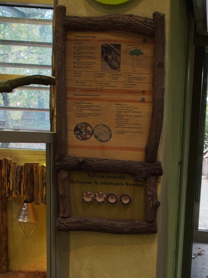 Foto: Eine mit halbrunden Ästen gerahmte Tegel mit Informationen in Schwarzschrift sowie im unteren Teil Lesepunkte für den Penfriend